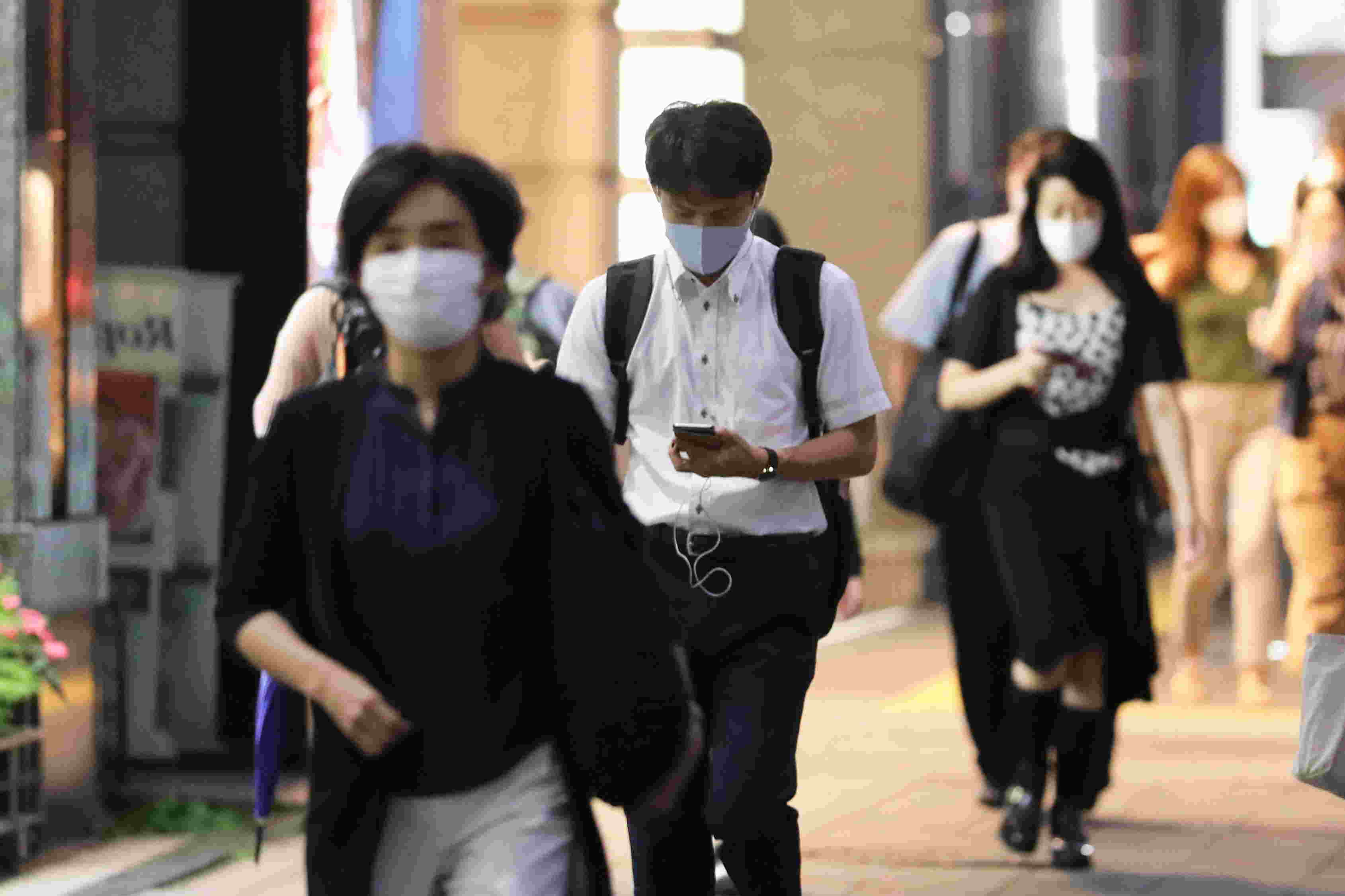 People wearing face masks walk on the street in Tokyo, last year (Xinhua/Du Xiaoyi/IANS)