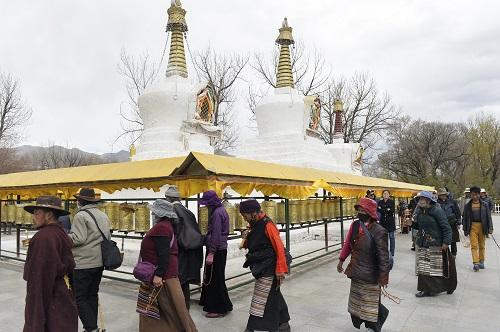Tibetan Buddhist believers walk around the Potala Palace for praying in Lhasa. Labeling the Chinese government and the CCP as